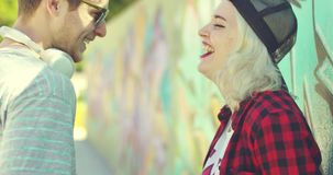 Two hipster friends chatting in front of graffiti stock video footage