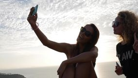 Two Hipster Girl Friends Making Selfie Photos on Smartphone. Lifestyle HD Slowmotion. stock video footage