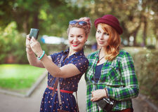 Two hipster girls with braces taking pictures of themselves on m Stock Photo