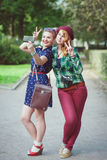 Two hipster girls with braces taking pictures of themselves on m Stock Photography
