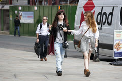 Two hipster girls dressed in cool Londoner style walking in Bric Stock Photography