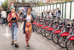Two hipster girls dressed in cool londoner style walking in Brick lane royalty free stock image