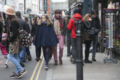 Two hipster girls dressed in cool Londoner style walking in Brick lane, a street popular among young trendy people Stock Images