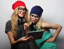 Two hipster girls friends use digital tablet Stock Images
