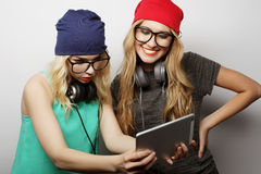 Two hipster girls friends use digital tablet Royalty Free Stock Images