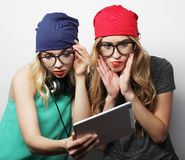 Two hipster girls friends use digital tablet Stock Photography