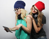 Two hipster girls friends use digital tablet Royalty Free Stock Photography