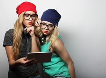 Two hipster girls friends use digital tablet Royalty Free Stock Photo