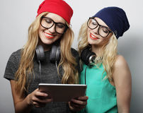 Two hipster girls friends use digital tablet Stock Photo