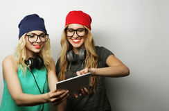Two hipster girls friends use digital tablet Royalty Free Stock Image