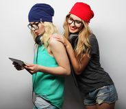 Two hipster girls friends use digital tablet Stock Photos