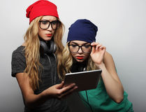 Two hipster girls friends use digital tablet Royalty Free Stock Photos