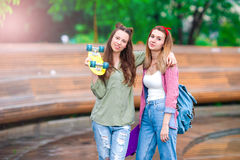 Two hipster girls with skateboard outdoors in sunset light. Active sporty women having fun together in skate park. Royalty Free Stock Image