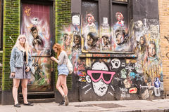 Two hipster girls standing in front of a wall covered in graffiti and murals Royalty Free Stock Photo