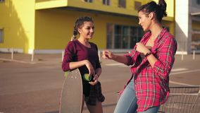 Two hipster girls standing by the shopping cart on parking by the citymall during sunset. Girl in plaid shirt is. Two attractive hipster girls standing by the stock video