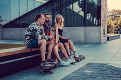 Two hipster males and blond female with longboards resting. Two males and one female with longboards posing on the street in urban style Stock Photos
