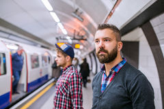 Two hipster men standing at the underground platform waiting Royalty Free Stock Images
