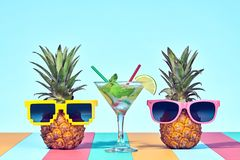 Two Hipster Pineapple in Sunglasses on Beach. Two Hipster Fruits in Trendy Sunglasses, Cocktail on Beach. Tropical Pineapple. Bright Summer Color.Fashion Style stock photography