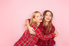 Two hipster woman listening music on the wireless headphones and dancing royalty free stock photos