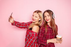 Two hipster woman posing, listening music by wireless headphones and making selfie by smartphone on the pink royalty free stock photos