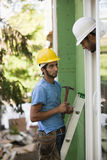 Two hispanic carpenters inspecting a window installation Royalty Free Stock Images