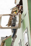 Two hispanic carpenters lifting a window frame Stock Photos