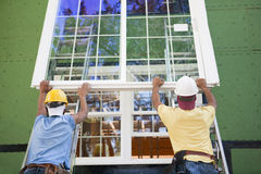 Two hispanic carpenters lifting a window. Hispanic carpenters lifting a glass slider up on two parallel ladders for installation on upper level, all wearing stock photo