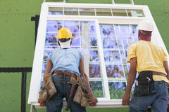 Two hispanic carpenters lifting a window for installation. Hispanic carpenters lifting a glass slider up on two parallel ladders for installation on upper level Stock Image
