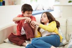 Two Hispanic Children Arguing. Over TV Remote Control Stock Photo