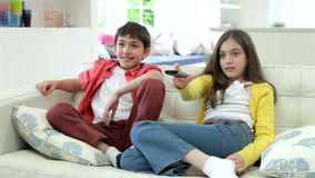 Two Hispanic Children Arguing Over TV Remote Control. Children sitting on sofa fighting over tv remote control.Shot on Canon 5d Mk2 with a frame rate of 25fps stock footage