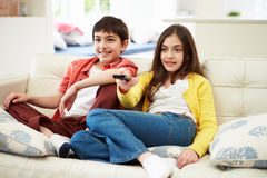 Two Hispanic Children Sitting On Sofa Stock Photo