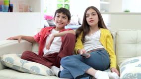 Two Hispanic Children Sitting On Sofa Watching TV Together