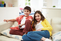 Two Hispanic Children Watching TV Together. Two Hispanic Children Sitting On Sofa Watching TV Together Stock Photo