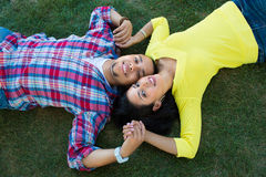 Two Hispanic Couple Lying on Grass Stock Photos
