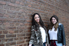 Two hispanic women against a brick wall. Royalty Free Stock Photography