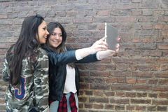 Two hispanic women taking a selfie with a tablet Royalty Free Stock Images