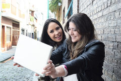 Two hispanic women taking a selfie with a tablet Stock Photos