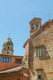 Two historic brick churches with towers in contrast to more modern orange house in Siena, Italy, Europe.  royalty free stock photography