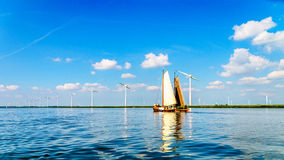 Two Historic Wooden Botter Boats in Full Sail near a Wind Farm along the Shore of Veluwemeer Stock Photography
