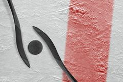 Two hockey sticks, a puck and a fragment of the ice arena with a. Two sticks, a puck, a red line and a background hockey arena. Concept, hockey stock photo