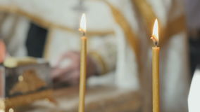 Two holy candles, priest reciting the prayer from bible on blurred background. Close-up. Two holy candles on foreground. Male`s hand is touching the holy book on stock video footage