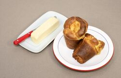 Two Home Baked Popovers And A Stick Of Butter Stock Photo