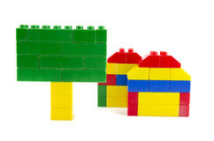 Two home icon made from plastic building blocks and green signage Royalty Free Stock Photos