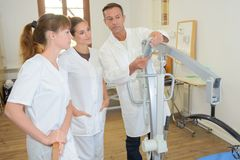 Two homecare nurses learning how to use hoist. Two homecare nurses learning how to use a hoist royalty free stock images