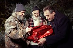 Two homeless men rewarding man in suit for gift of food in christmas time royalty free stock photo