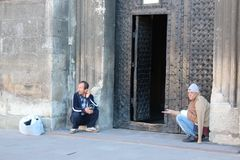 Two homeless people earn their living by begging at church doors Royalty Free Stock Images