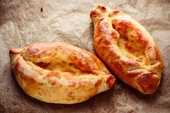 Two homemade ajarian khachapuri on wooden table royalty free stock photography