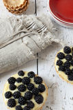 Two homemade blackberries tart with pastry cream on wooden table with cloth, fork and little plate Royalty Free Stock Photos