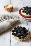 Two homemade blackberries tart with pastry cream on wooden table with cloth, fork and little plate Stock Photography