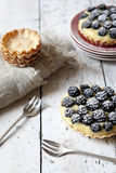 Two homemade blackberries tart with pastry cream on wooden table with cloth, fork and little plate Stock Images